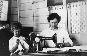Violet's daughter, Ailsa Trundle is working on a small sewing project beside her mother. Image from State Library of Queensland, via Wikimedia Commons.