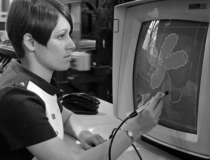 """<strong>A woman uses a """"light pen"""" to draw a design on a display terminal</strong><div>1968. A woman uses a"""