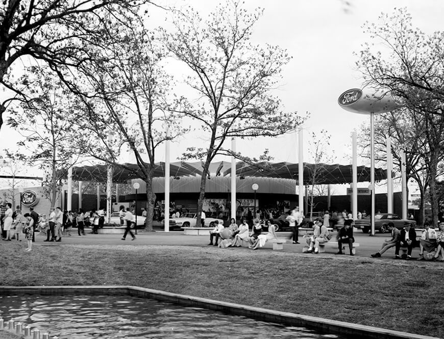 <strong>Outside of the Ford Motor Company Pavilion</strong><div>April 1968. People resting on benches overlooking a waterway outside the Ford Motor Company Pavilion at HemisFair'68.</div>